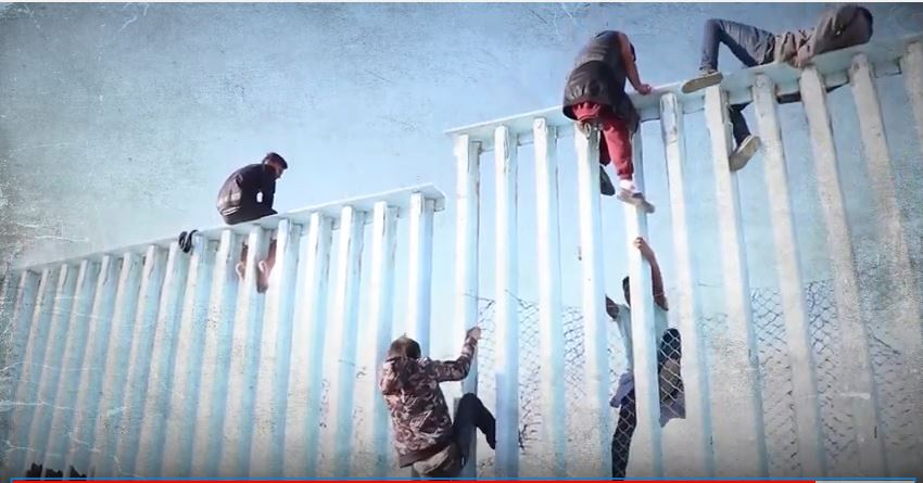 People scaling border wall