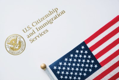 U.S. Citizen and Immigration Service logo and American flag
